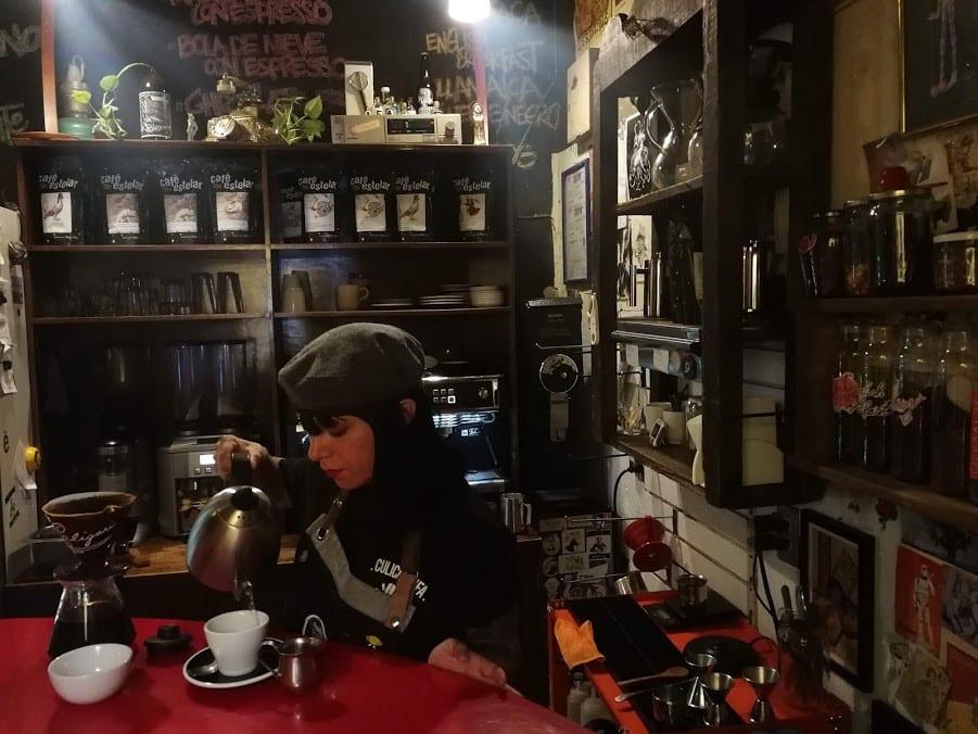Una barista prepara un cafe para cliente