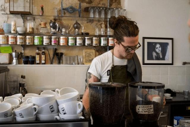 barista detras de la barra de cafe