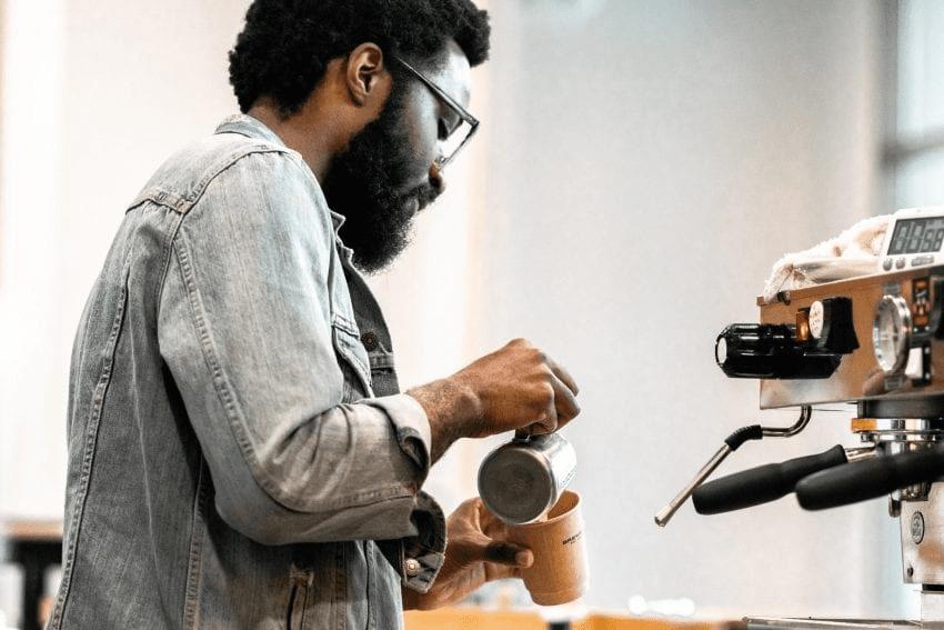 un barista prepara cafe para un cliente