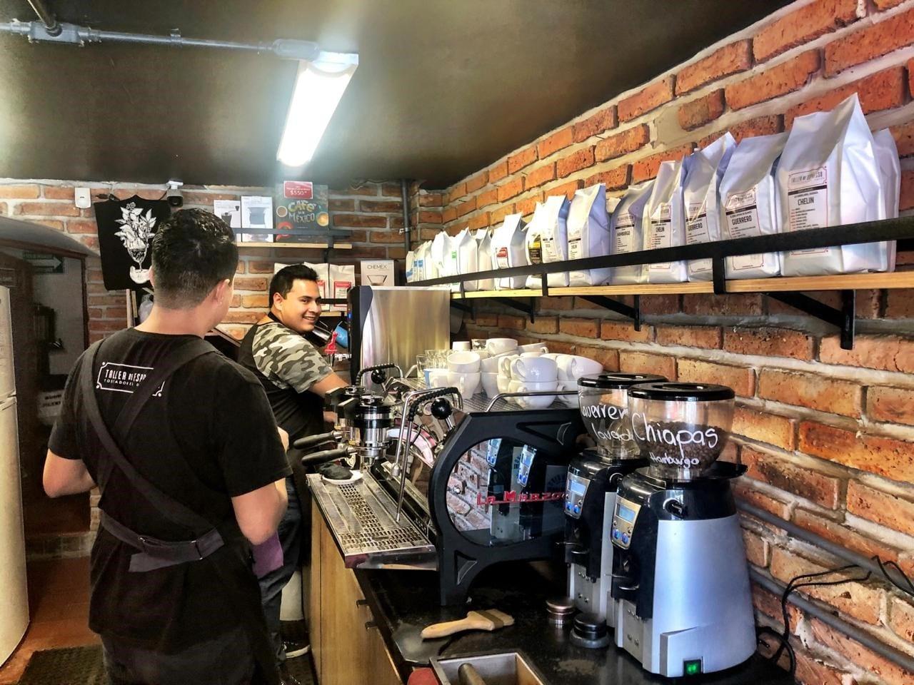 Baristas detras de una barra preparando cafes