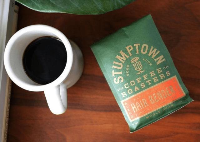 una bolsa de cafe junto a una taza de cafe fresca