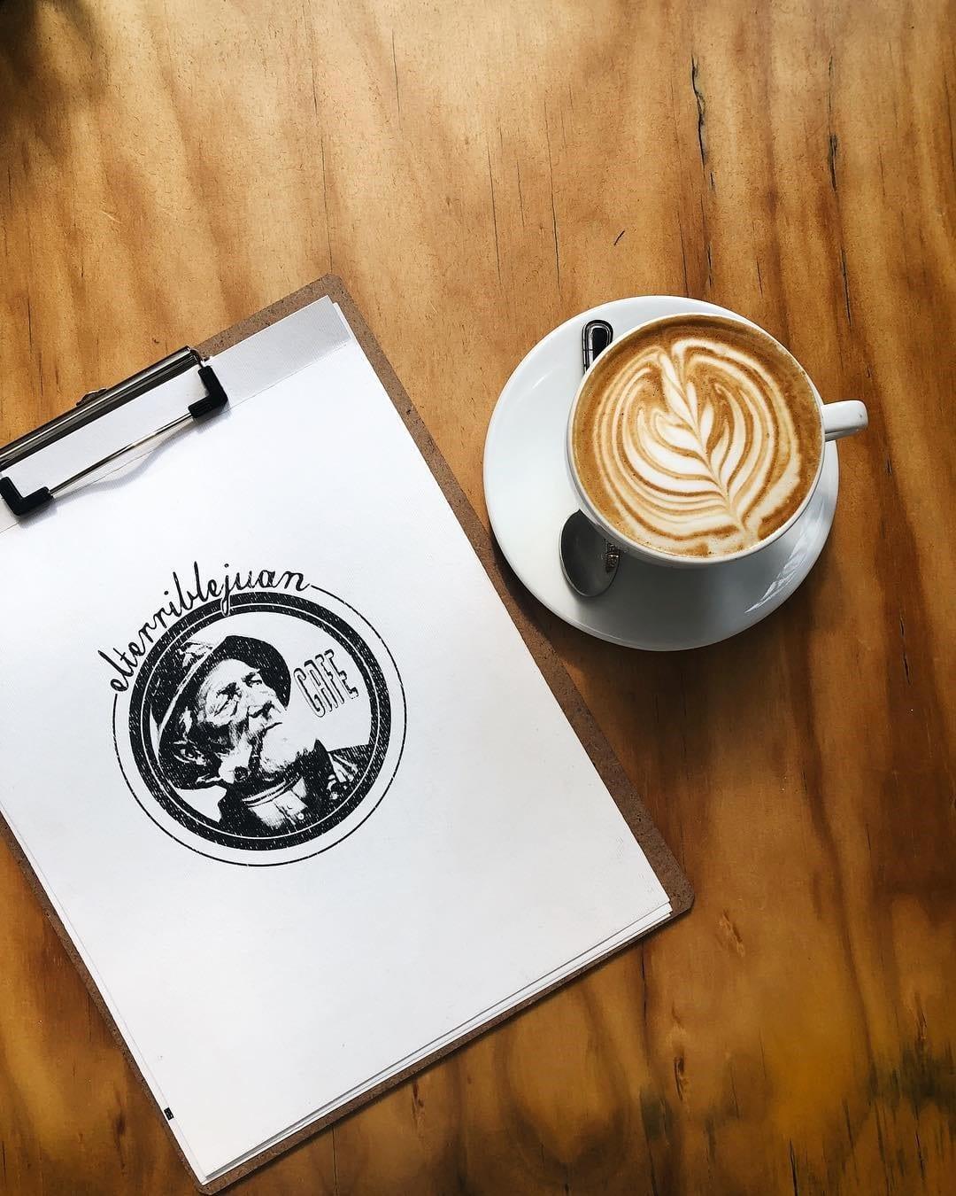 el menu de una cafeteria junto a un cappuccino