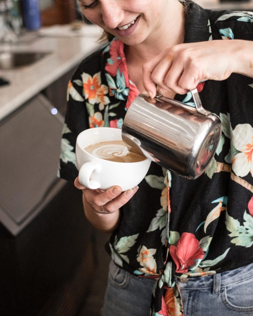 una barista preparando un cappuccino con arte latte