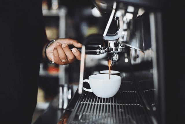barista prepara dos espressos para hacer cappuccino