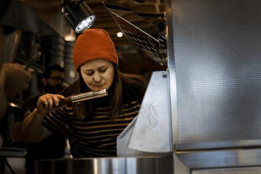 una mujer tostadora tostando sus cafes