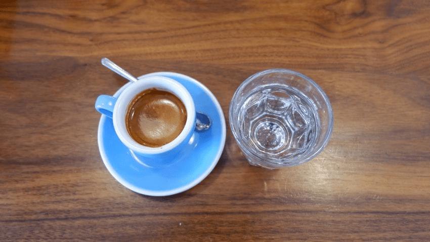un espresso bien hecho y un vaso de agua