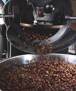 freshly roasted coffee falling into cooling tray