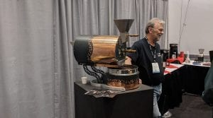 joe behm at the behmor stand next to a copper roaster