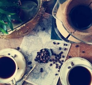 coffee beans, chemex and cups on a world map