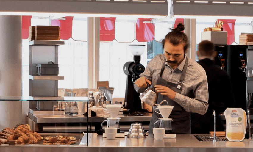 un barista prepara un cafe para un cliente