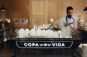 barista behind espresso machine brewing coffee