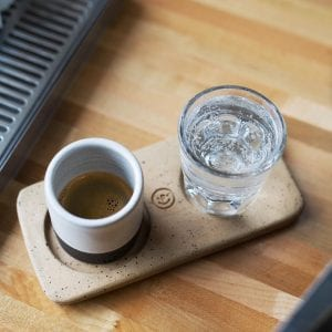 a shot of espresso and a glass of water