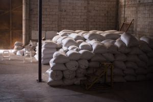 Bags of green coffee sit in a warehouse