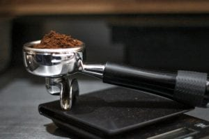 Ground coffee being weighted on a digital scale.